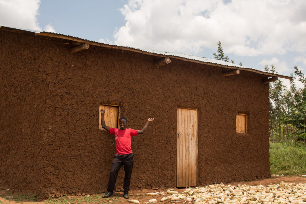 Rwanda boy in front of home